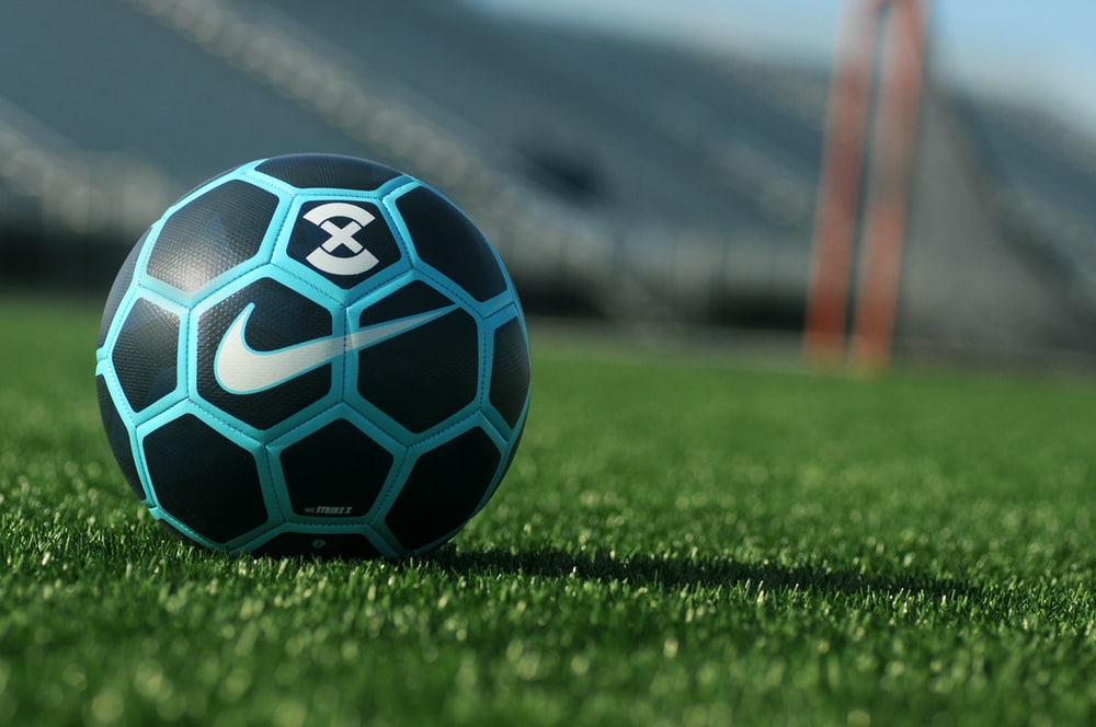 black, blue, and white Soccer ball on grass field