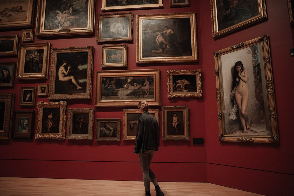 woman standing in front of paintings