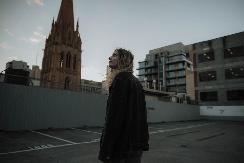 woman standing near cathedral looking at sky