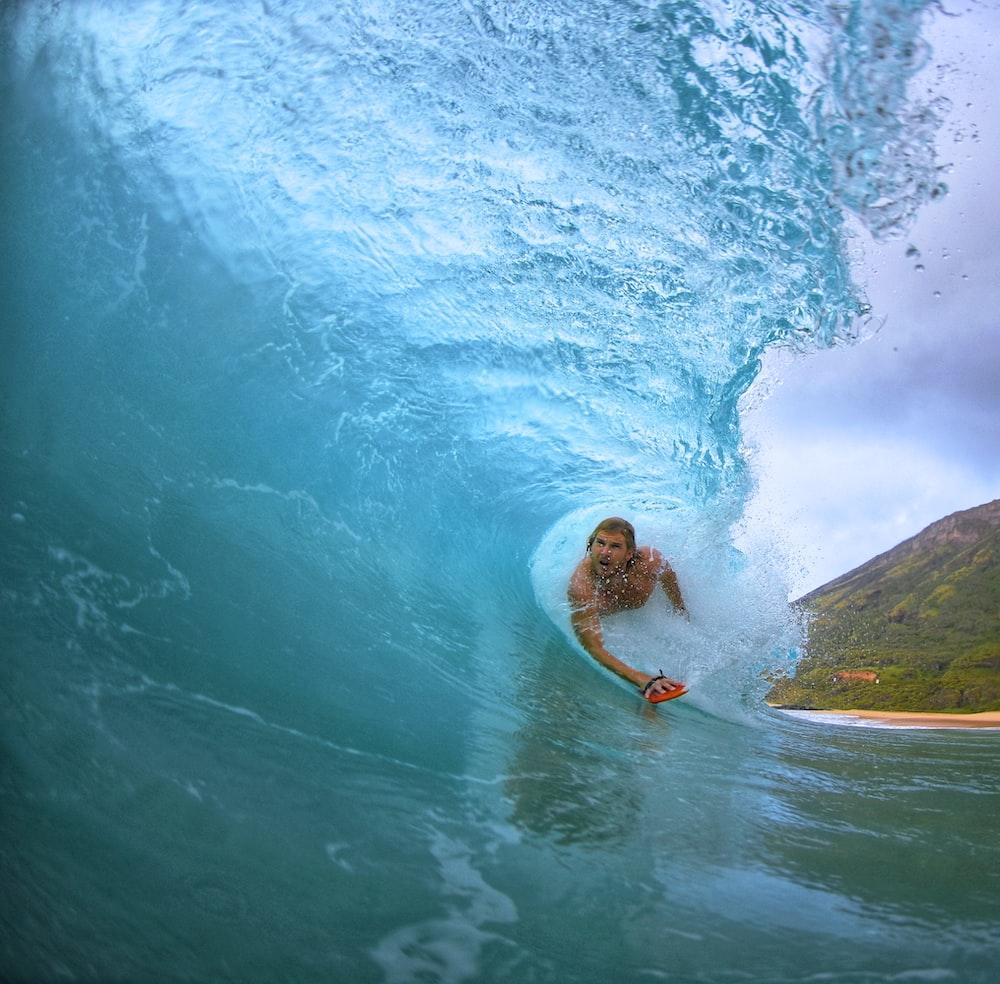 man surfing on seawaves during daytime