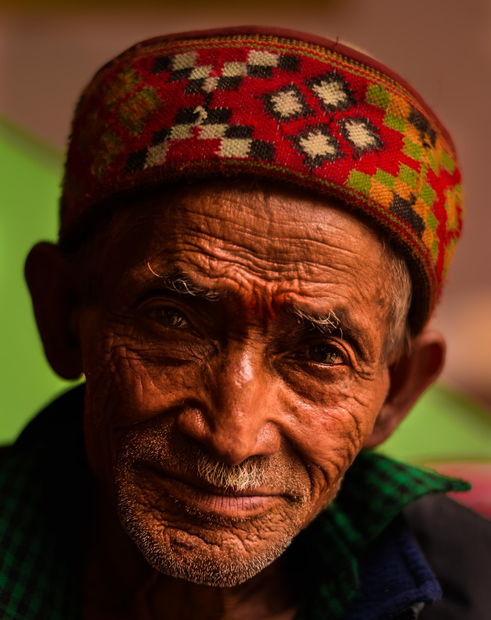 close-up photo of man wears red and multicolored traditional headdress