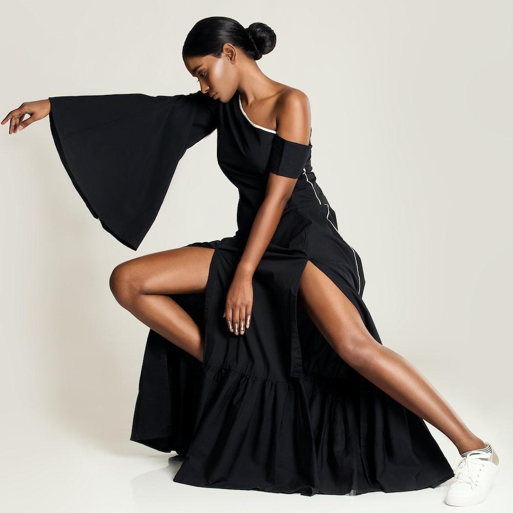woman in black one shoulder dress posing