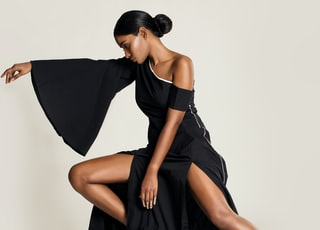 woman in black one shoulder dress posing