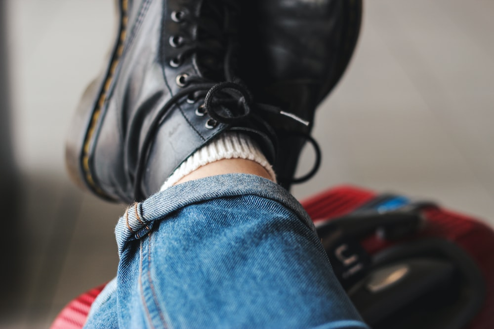 person wearing a pair of black work boots and blue jeans