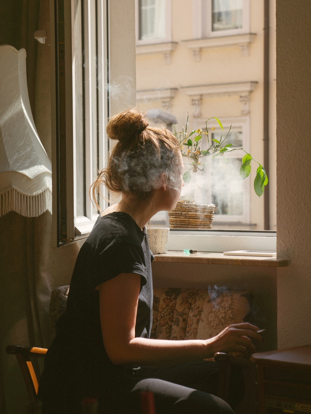 woman smoking while look through the window