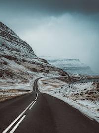 photograph of concrete road near mountain