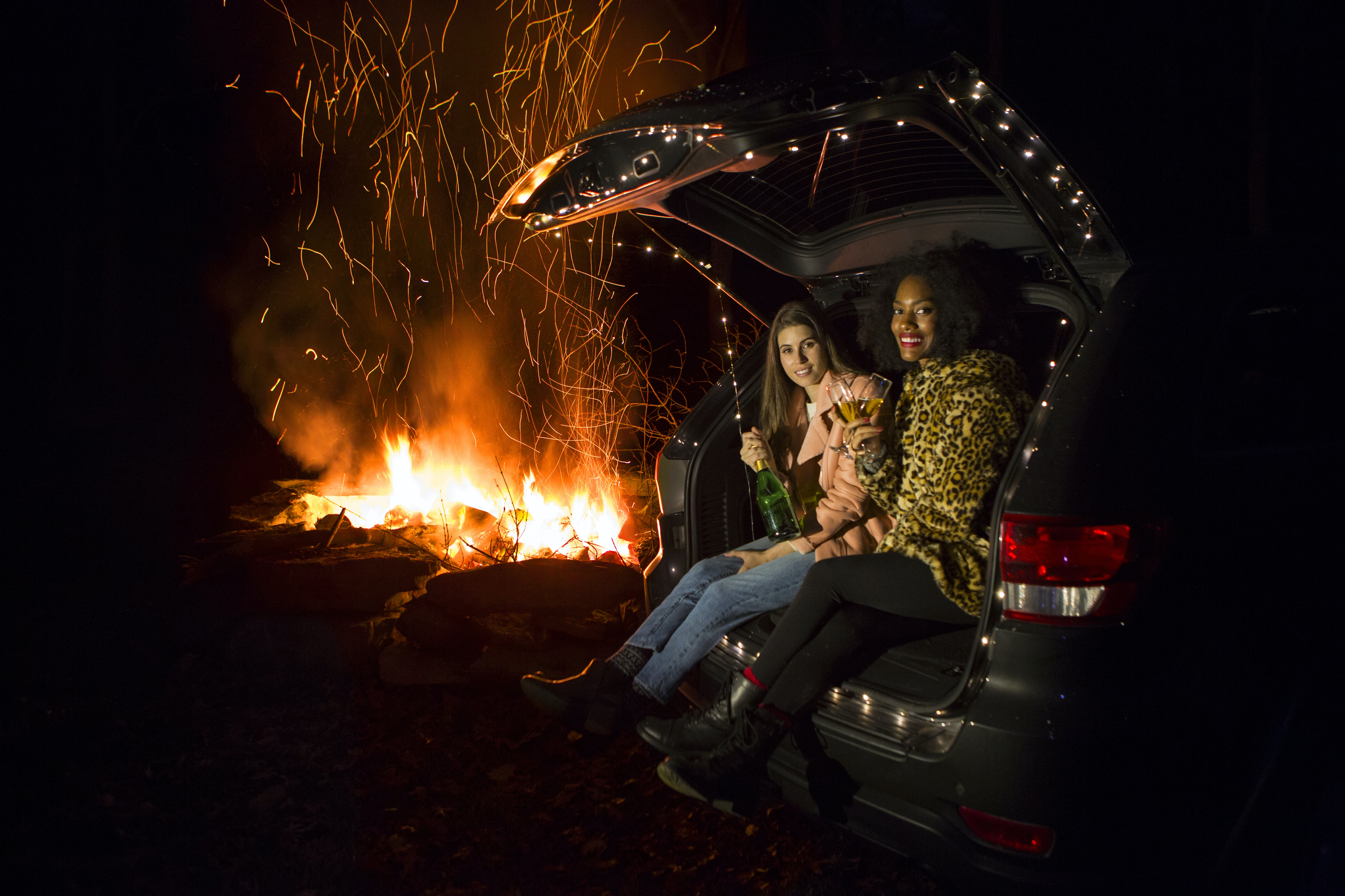 two women sitting on back of SUV near campfire