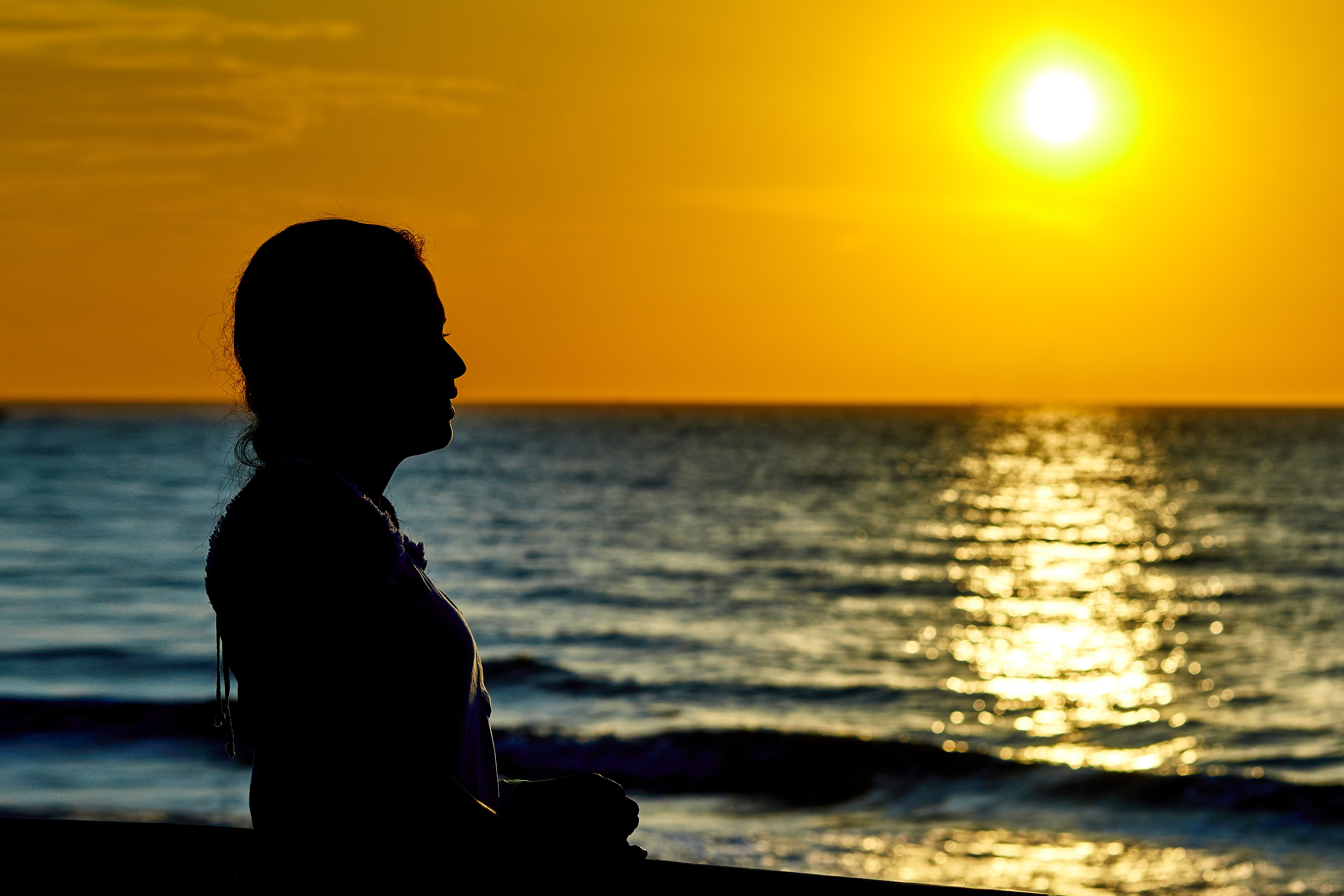 woman standing infront of beach during sunset
