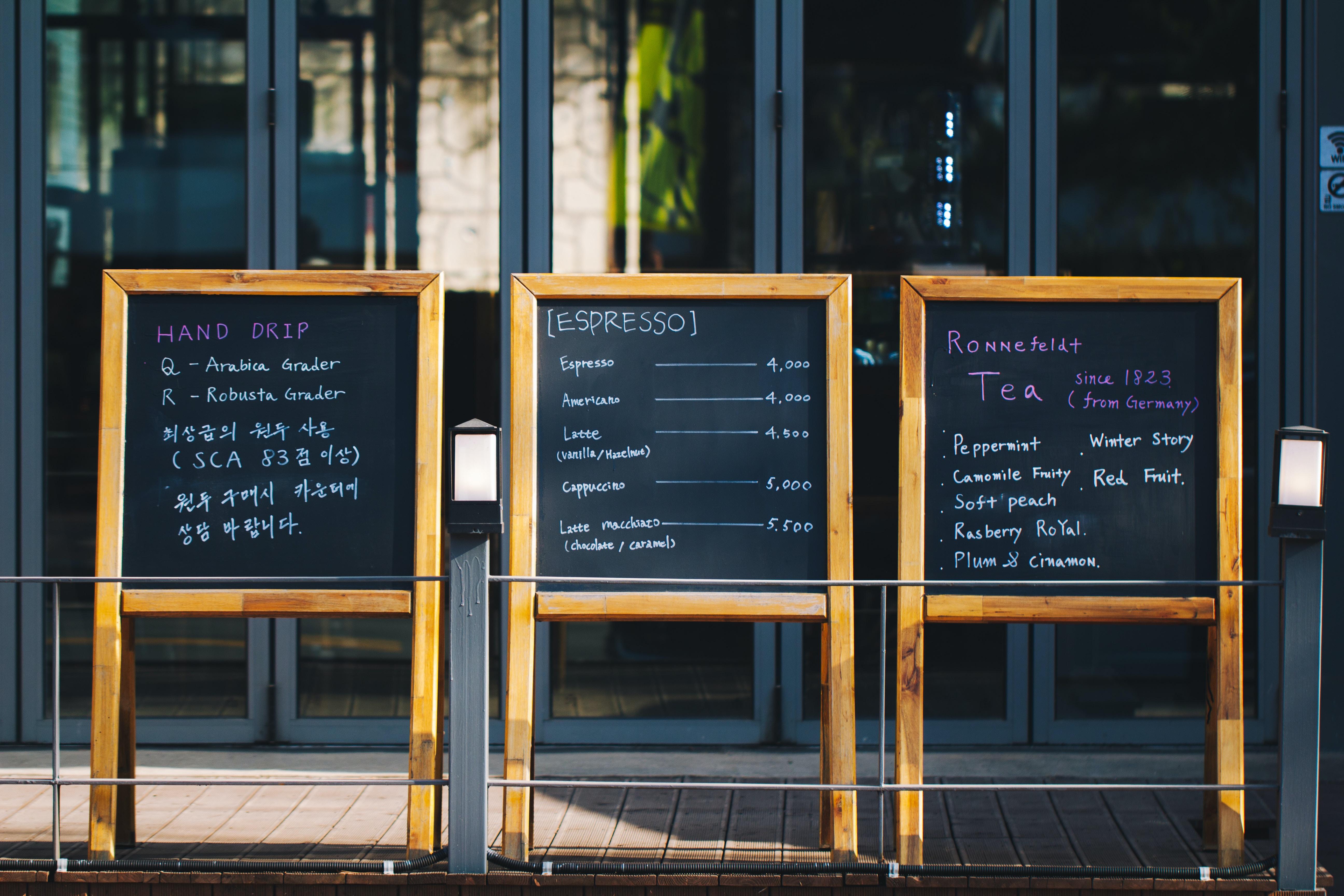 three wooden chalkboard in front of glass panel door