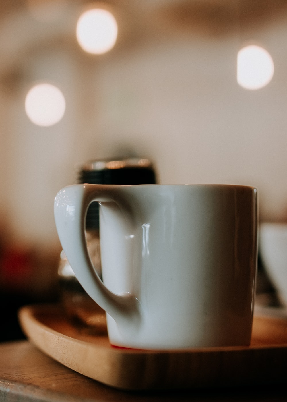 shallow focus photography of ceramic mug on wooden tray