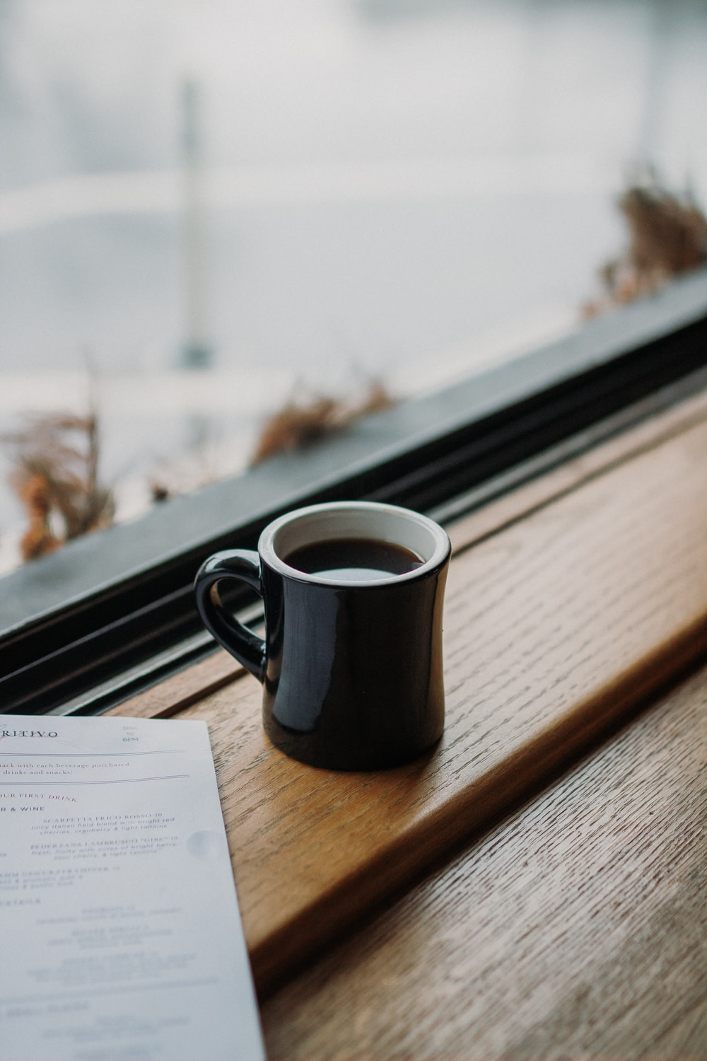 shallow focus photography of coffee cup beside glass window