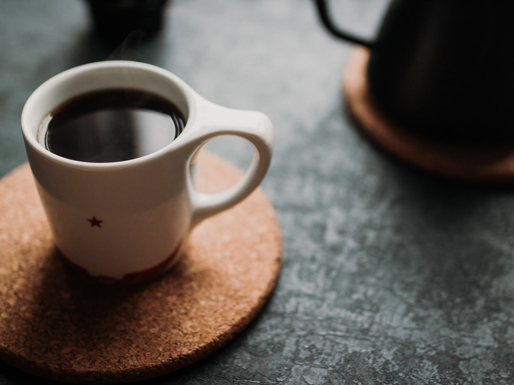 selective focus photograph of white mug filled with coffee