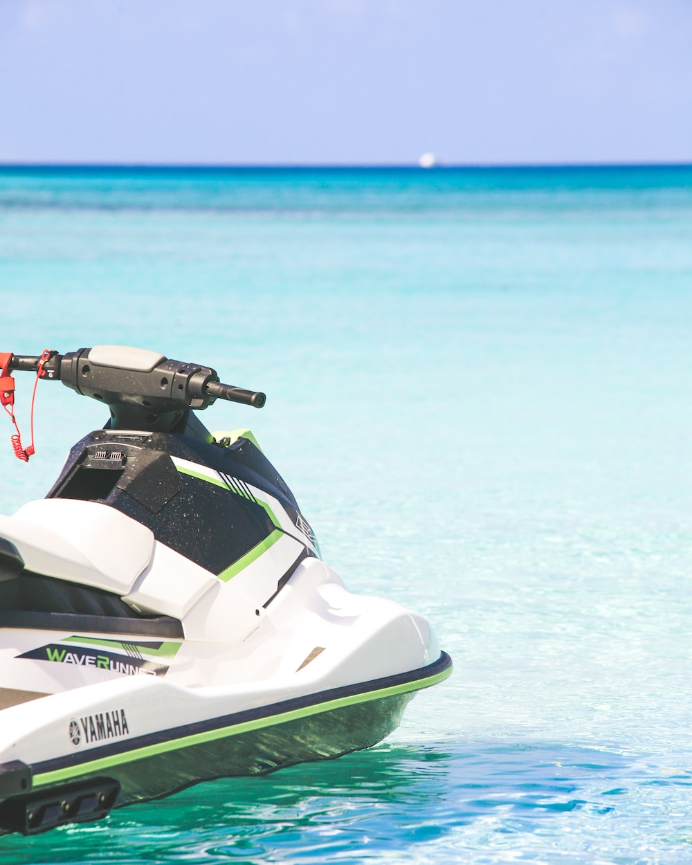 white and green personal watercraft on water