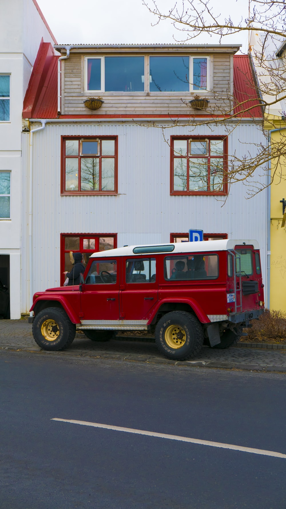 red vehicle beside house