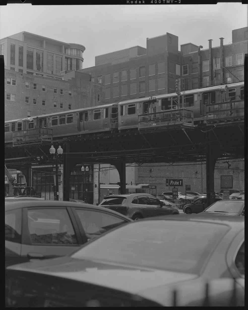 grayscale photography of cars under the trail rails