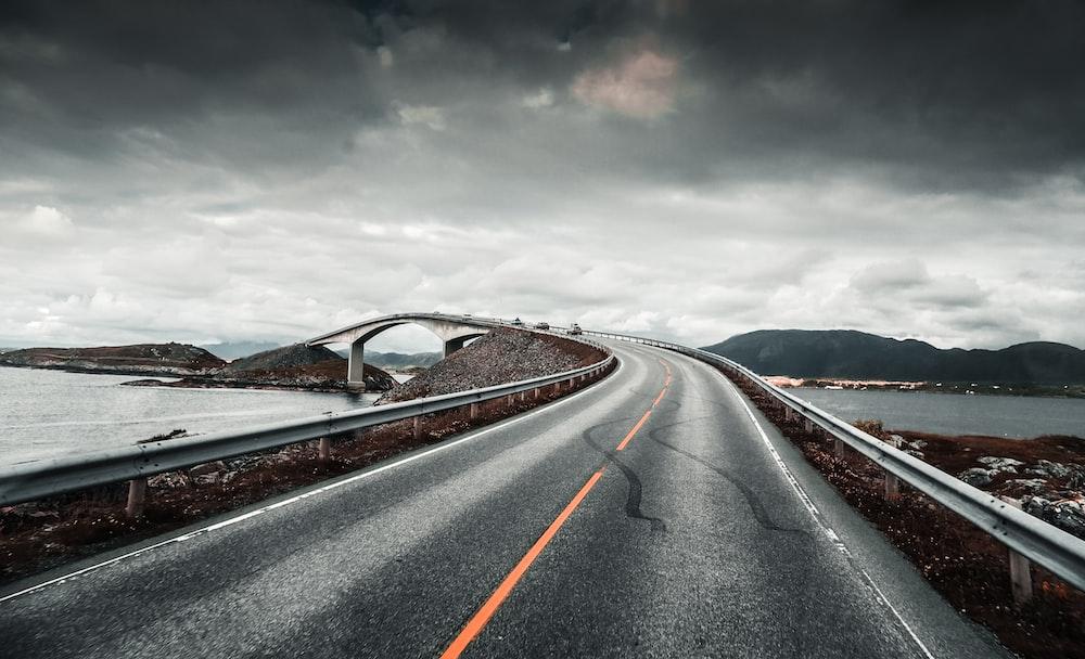 photo of asphalt road near body of water