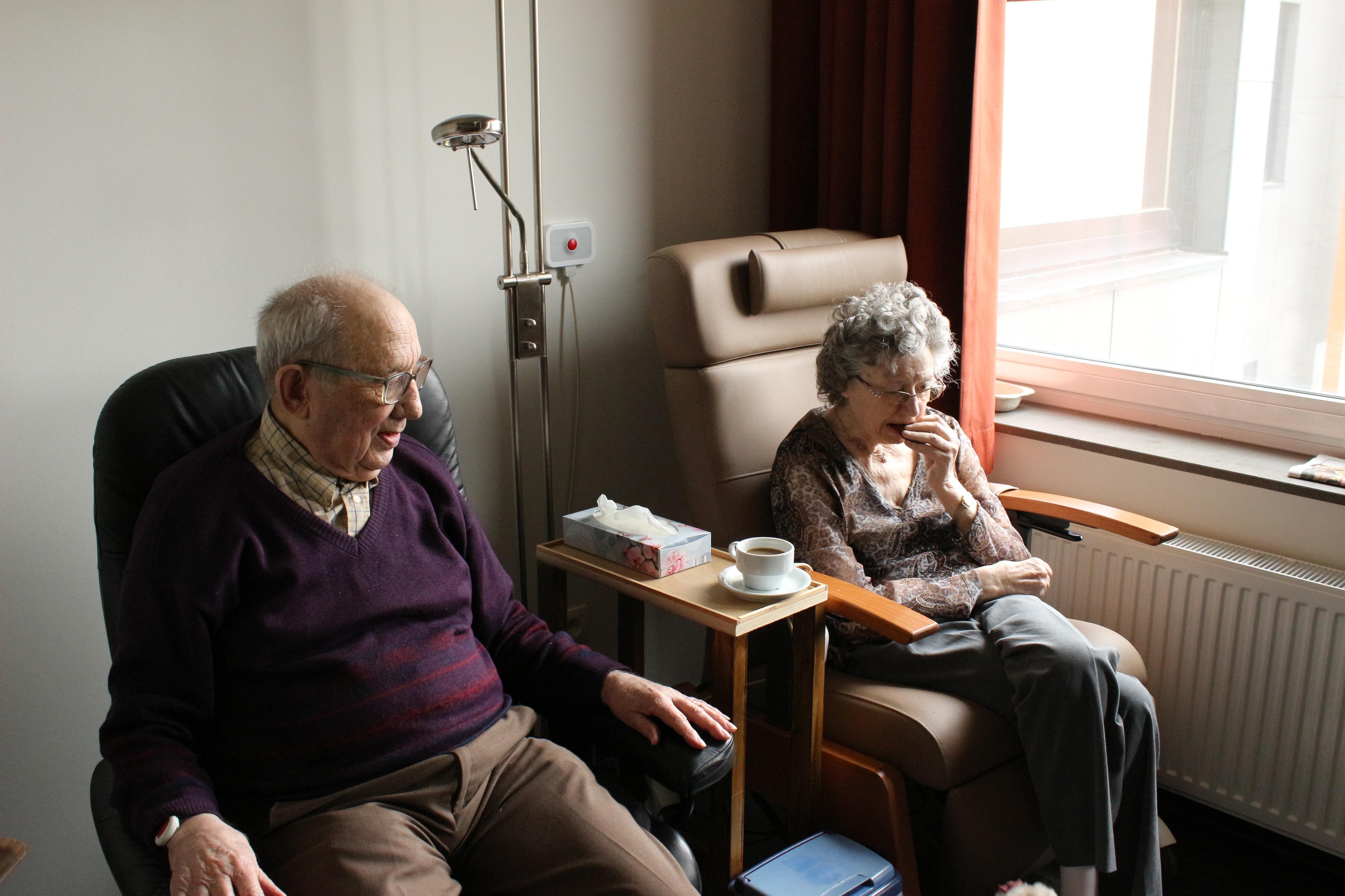 couple sitting side by side near panel radiator