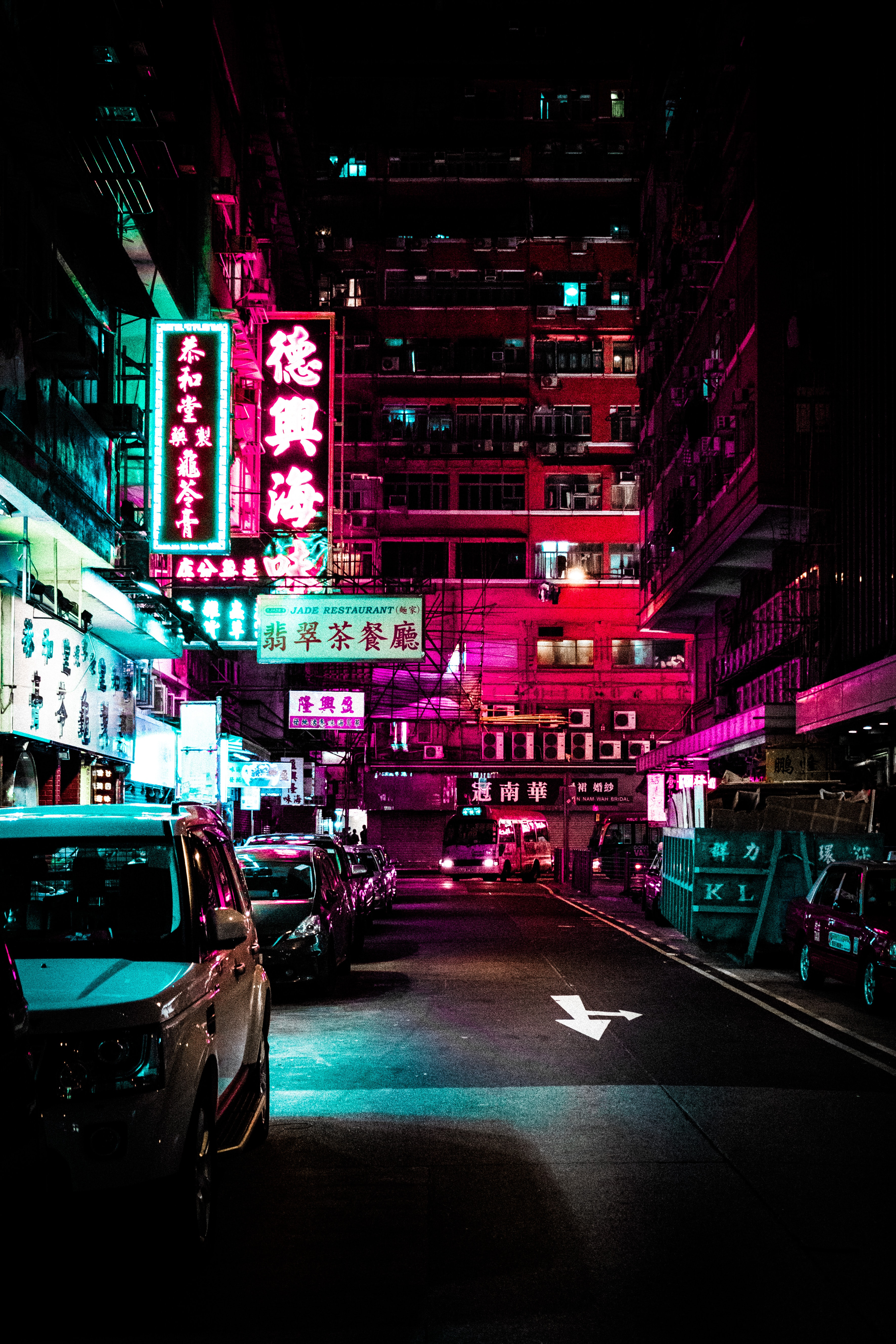 vehicles park on roadway between lighted buildings during nighttime