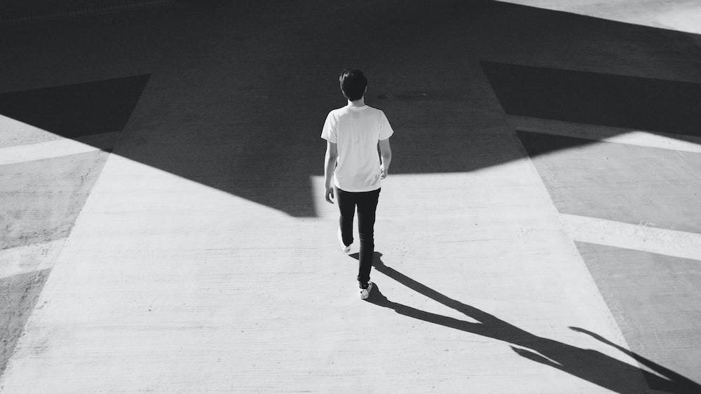 man walking on gray concrete road