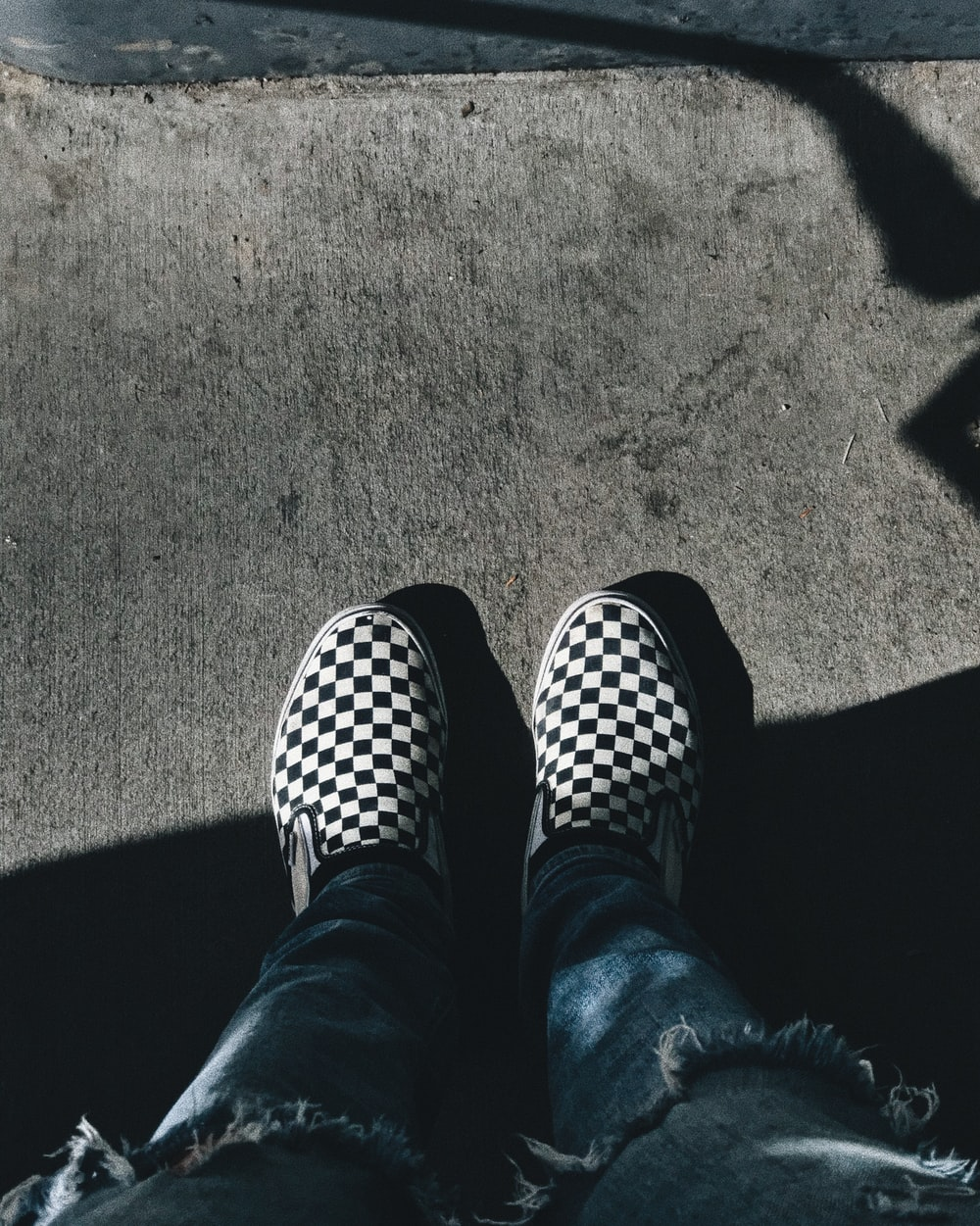 person standing while showing pair of black-and-white checkered shoes