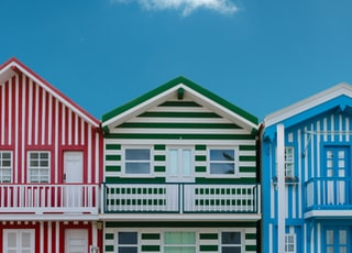 three assorted-color houses next to each other
