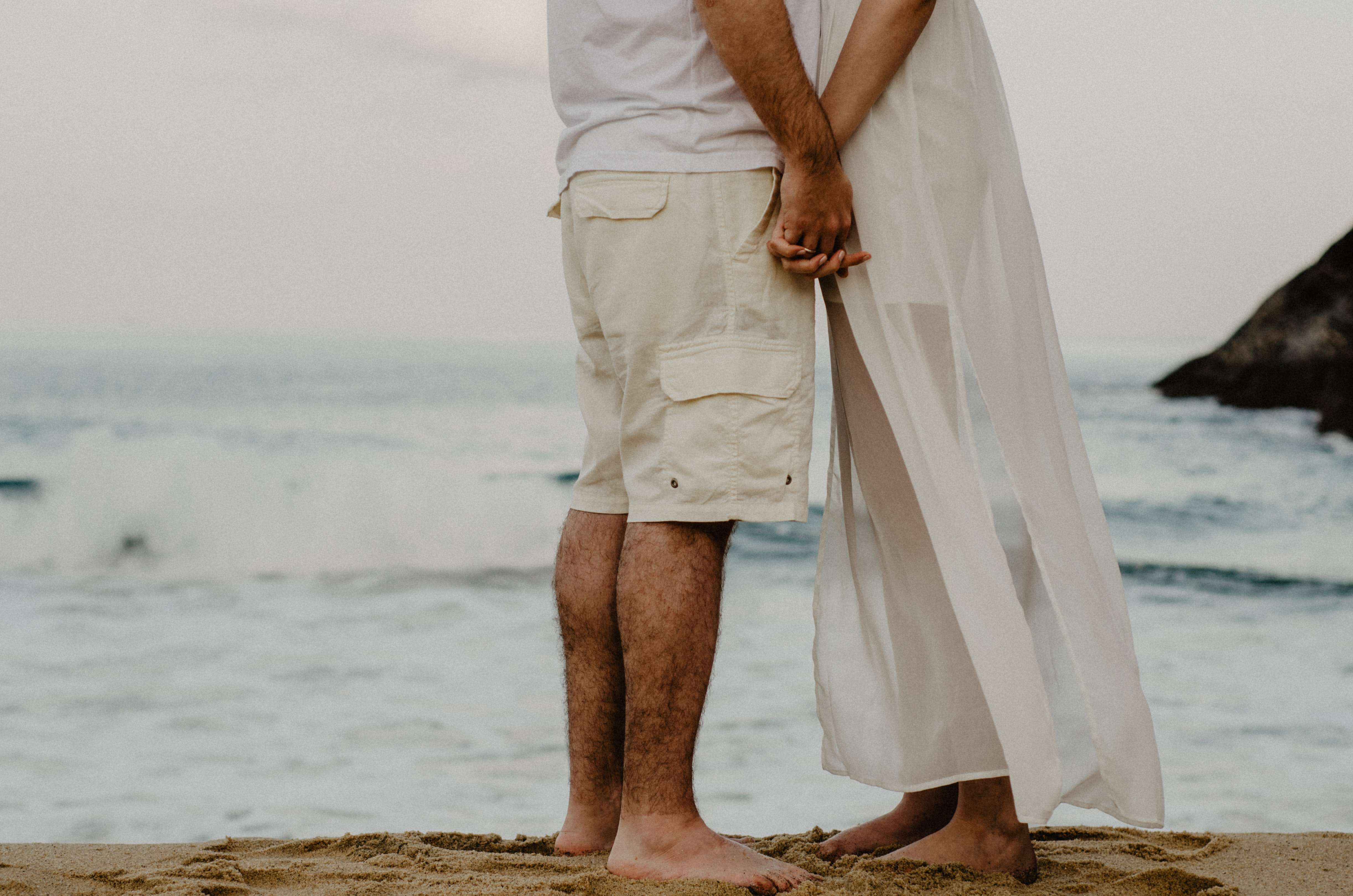 man and woman standing on seashore while holding hands