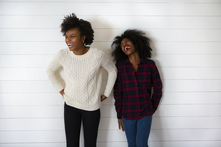 A photo of two Black women standing against a white wall with huge smiles. They are laughing.