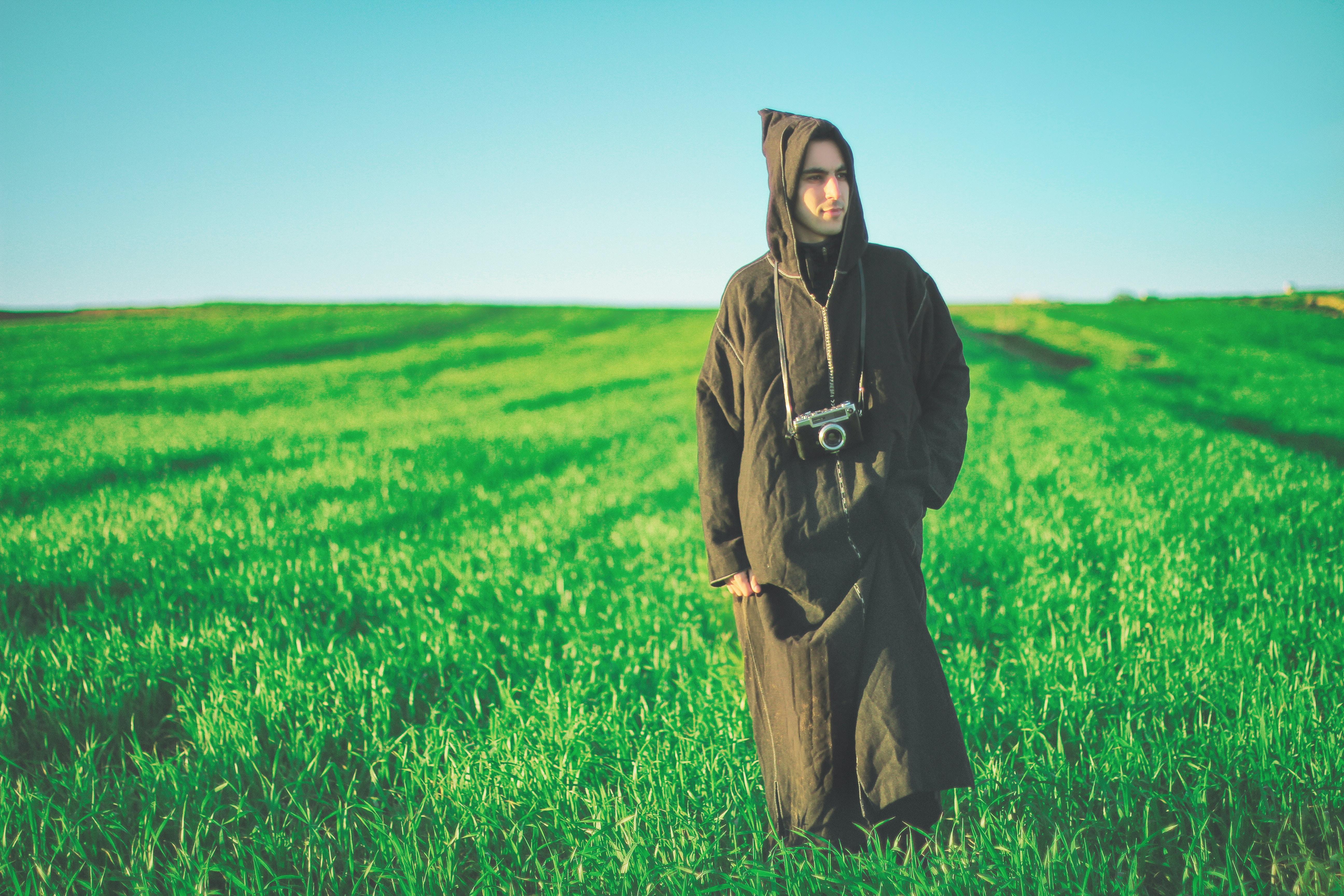 man in robe walking on green grass field