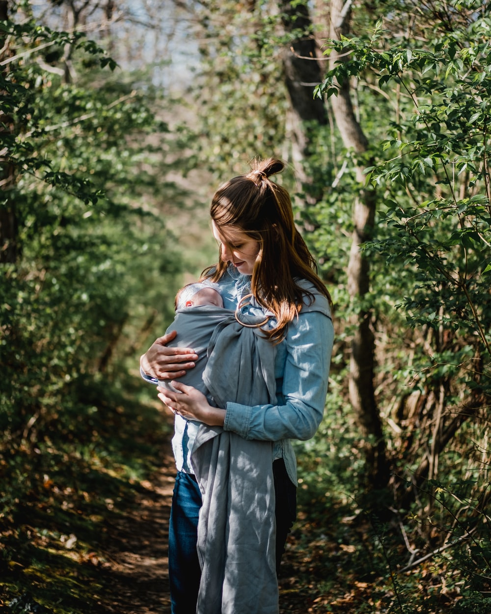 woman carrying child while standing near trees at daytime