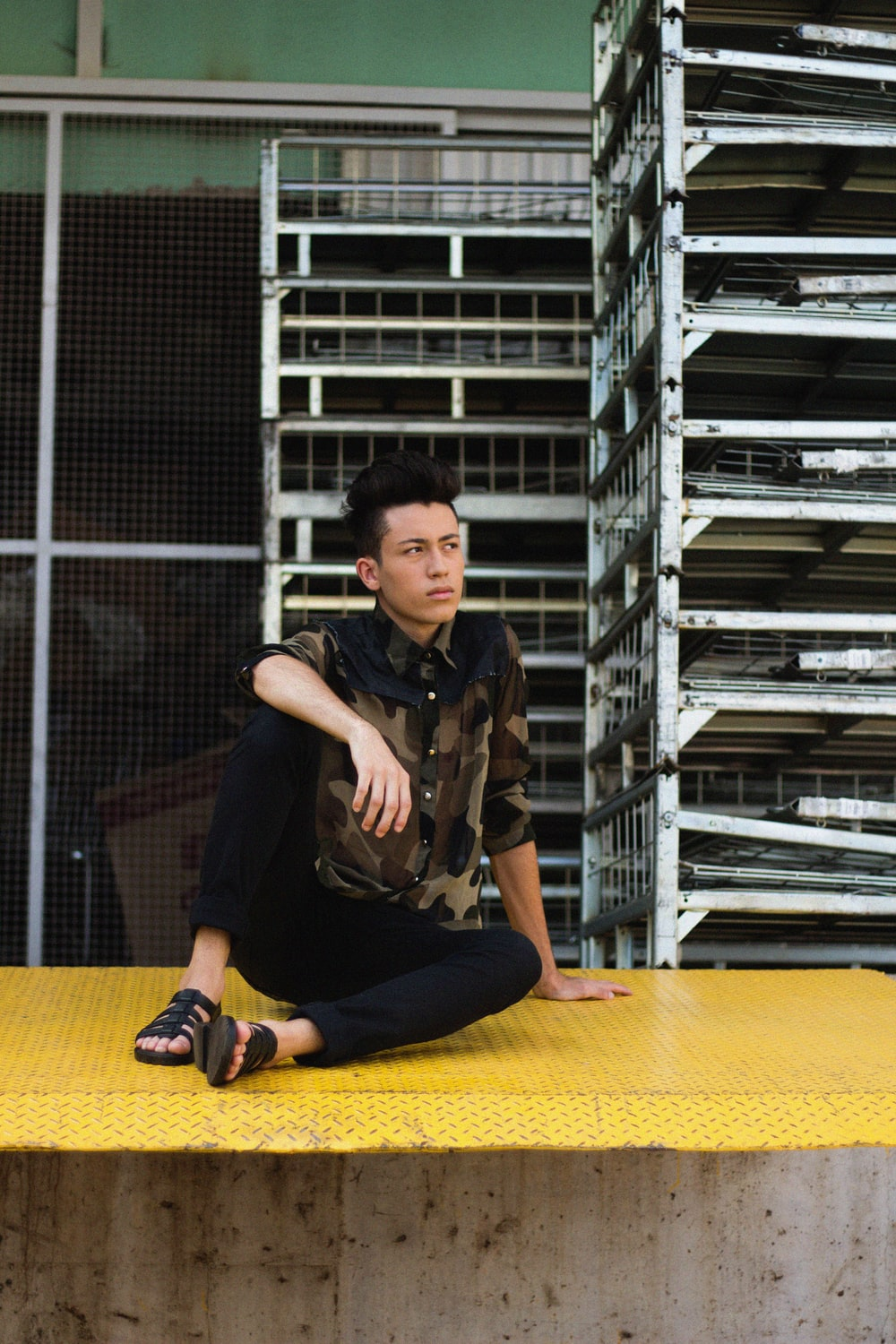 man sitting on yellow surface looking up