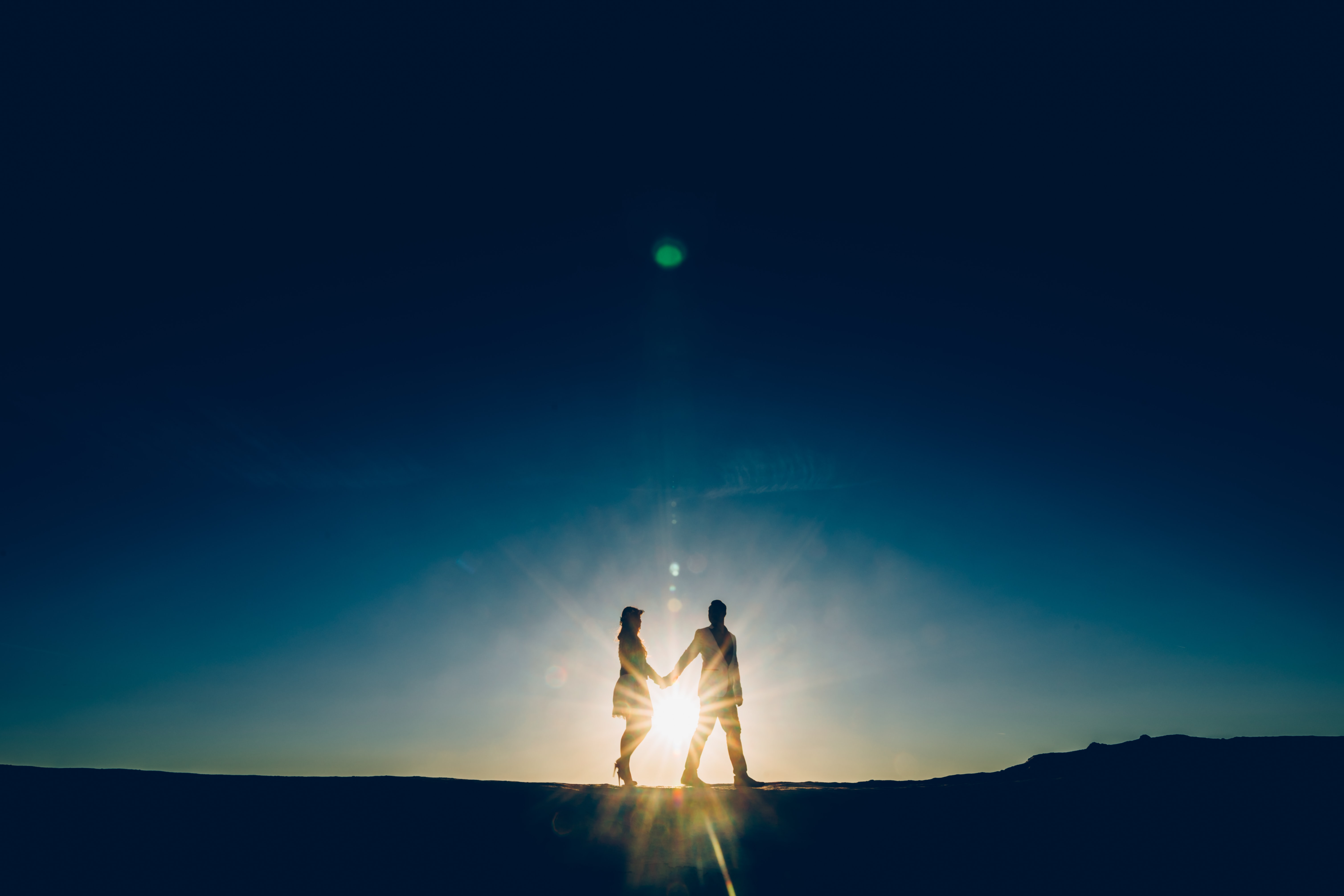 silhouette of two people holding each other's hand during golden hour