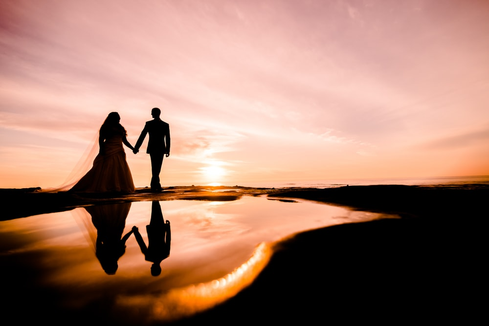 silhouette of male and female while holding hands