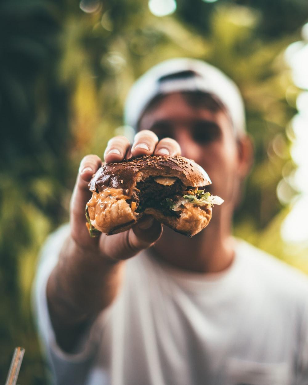 selective focus photography of man holding eaten burger