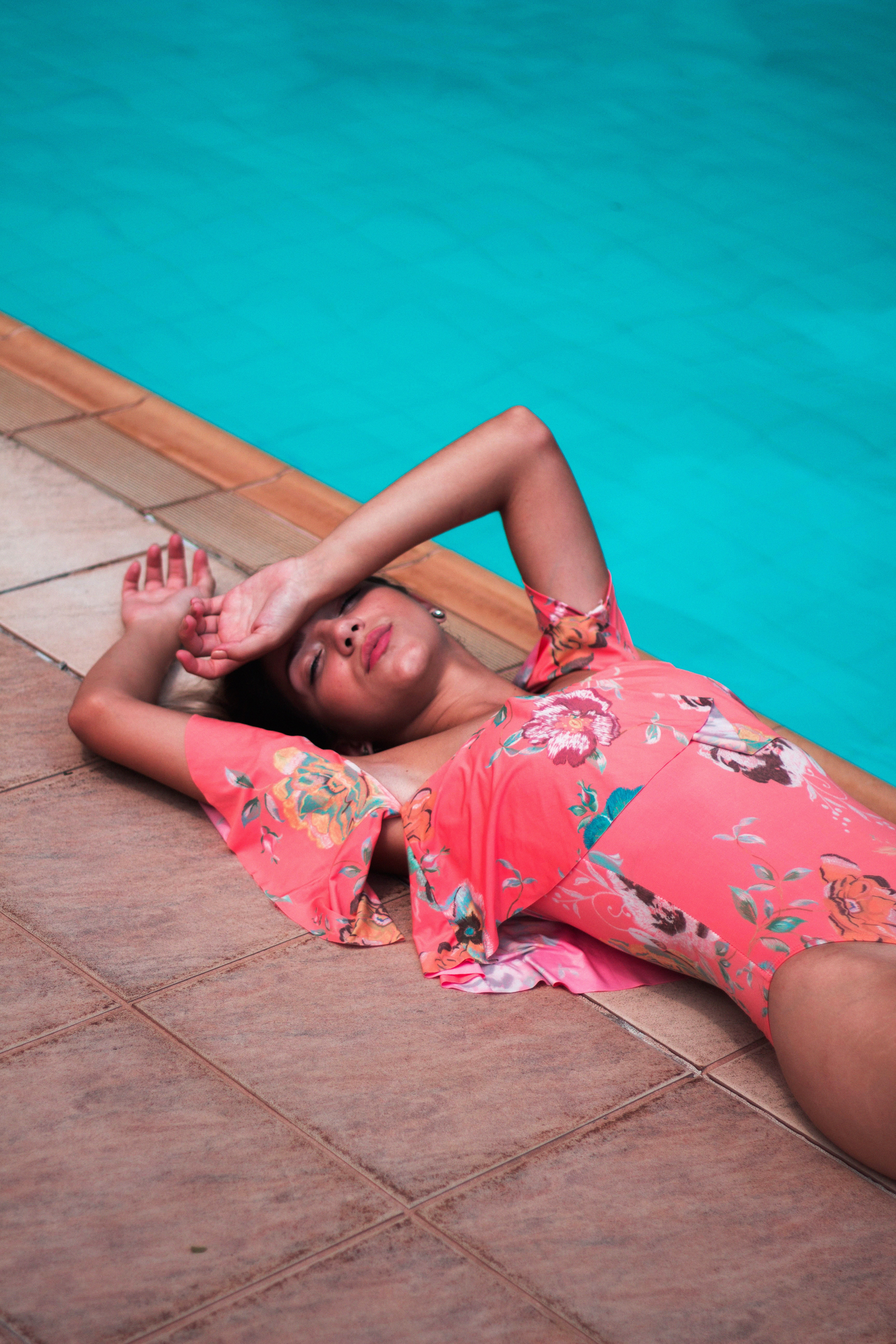 woman wearing pink floral swimsuit laying near gutter of in-ground pool