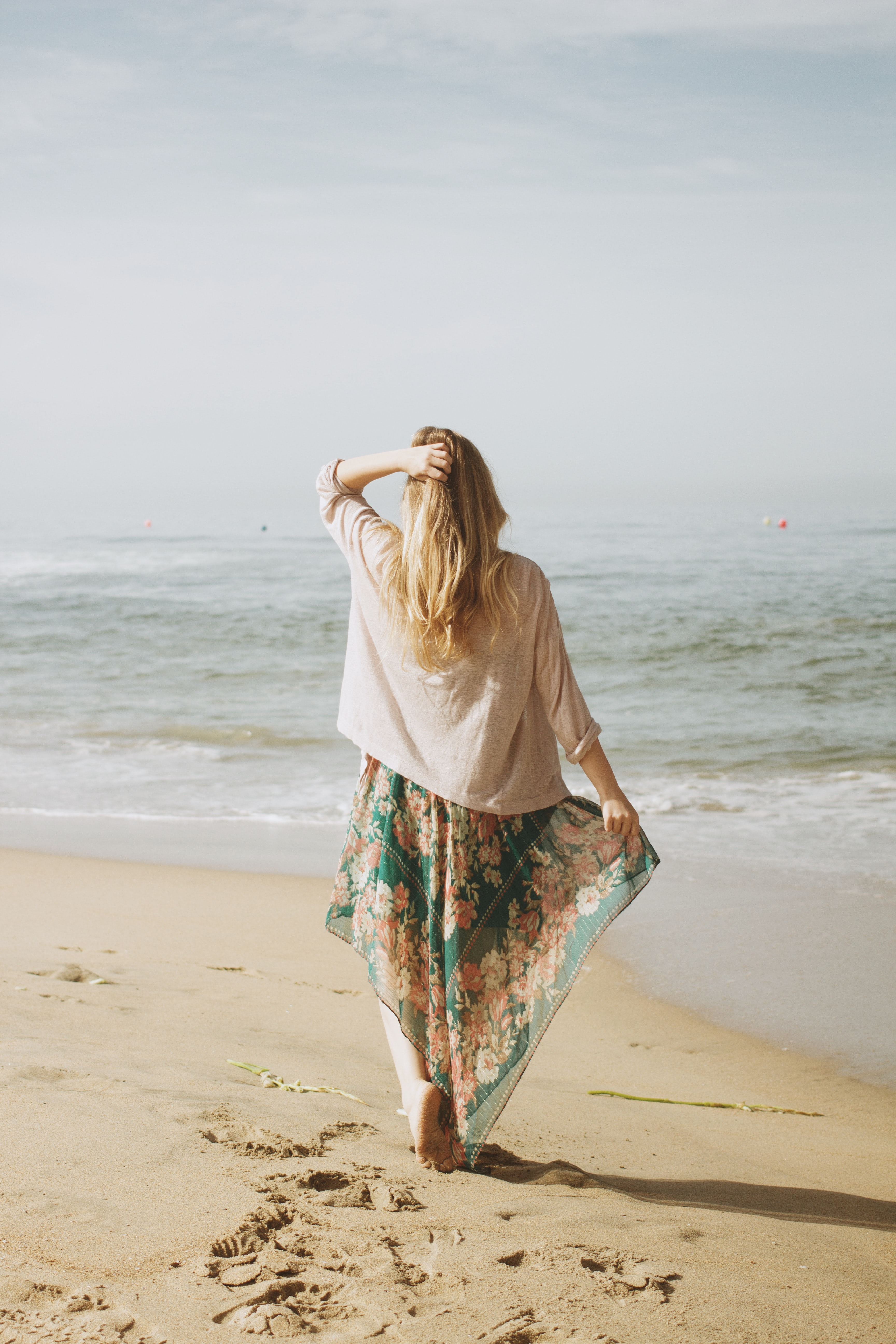 woman holding her skirt with her right arm and hair with left while standing on seashore