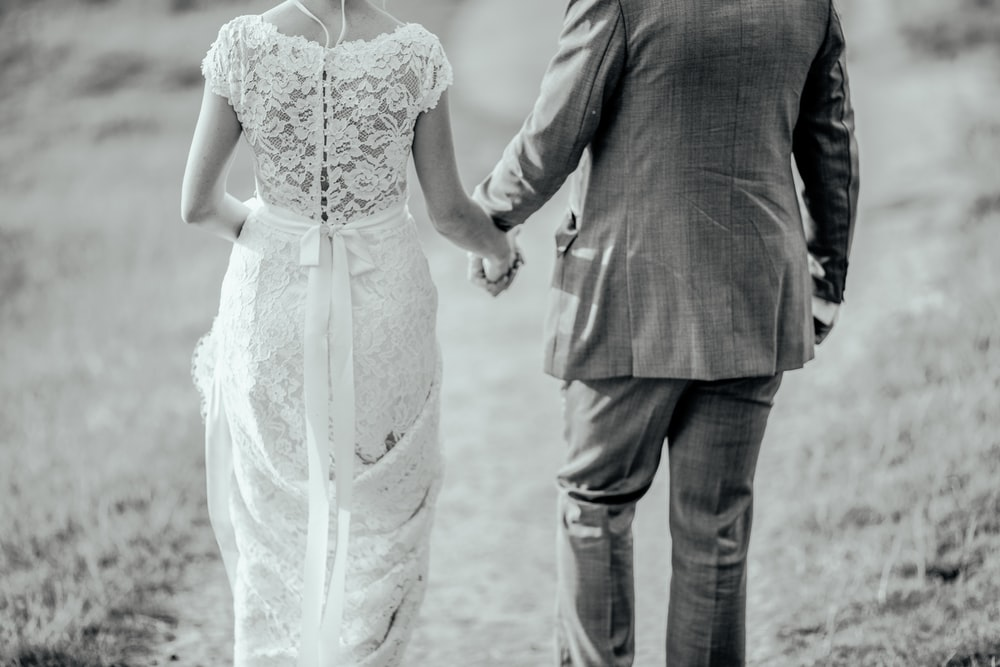 man and woman holding hands while walking on road