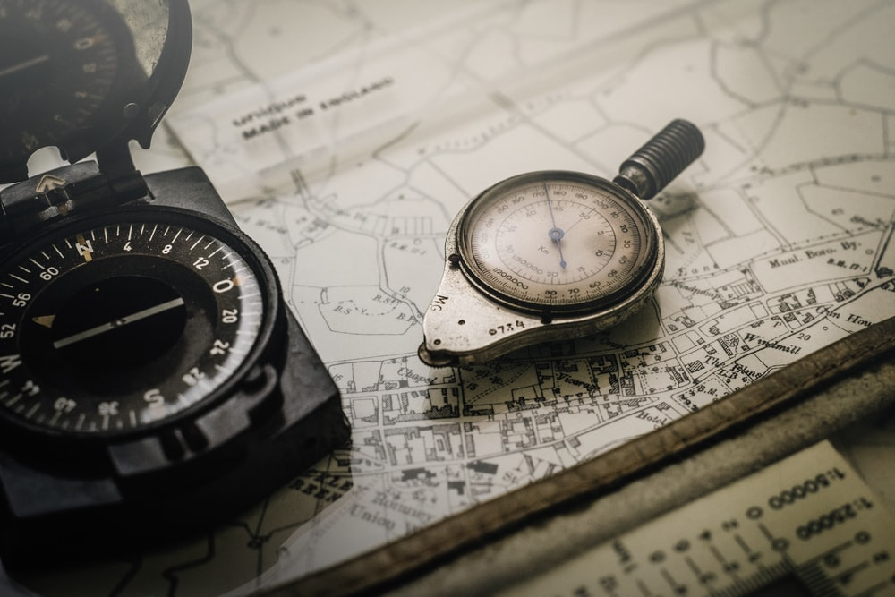 black and gray compass on top of map