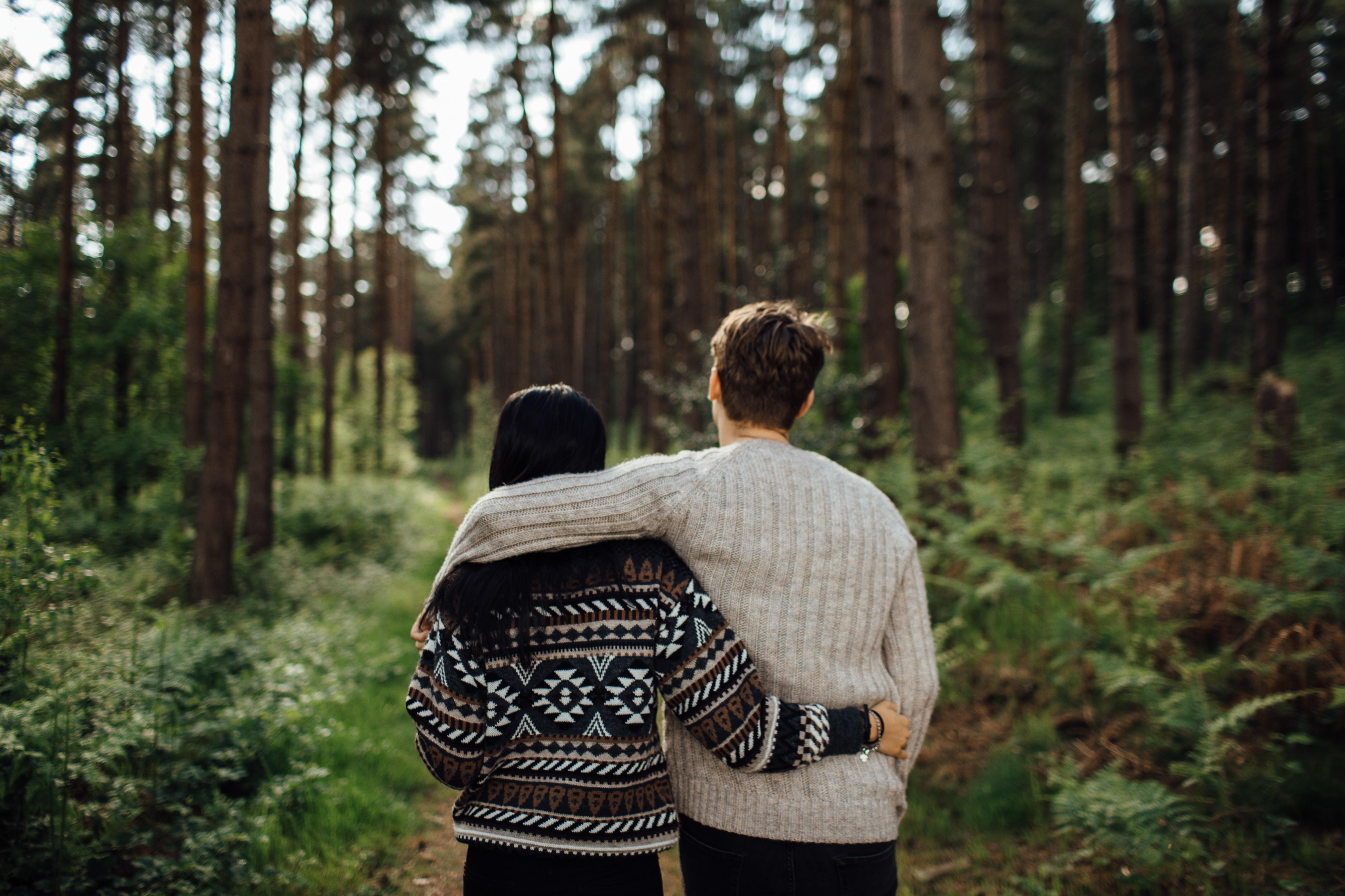 man's left arm over woman's shoulder