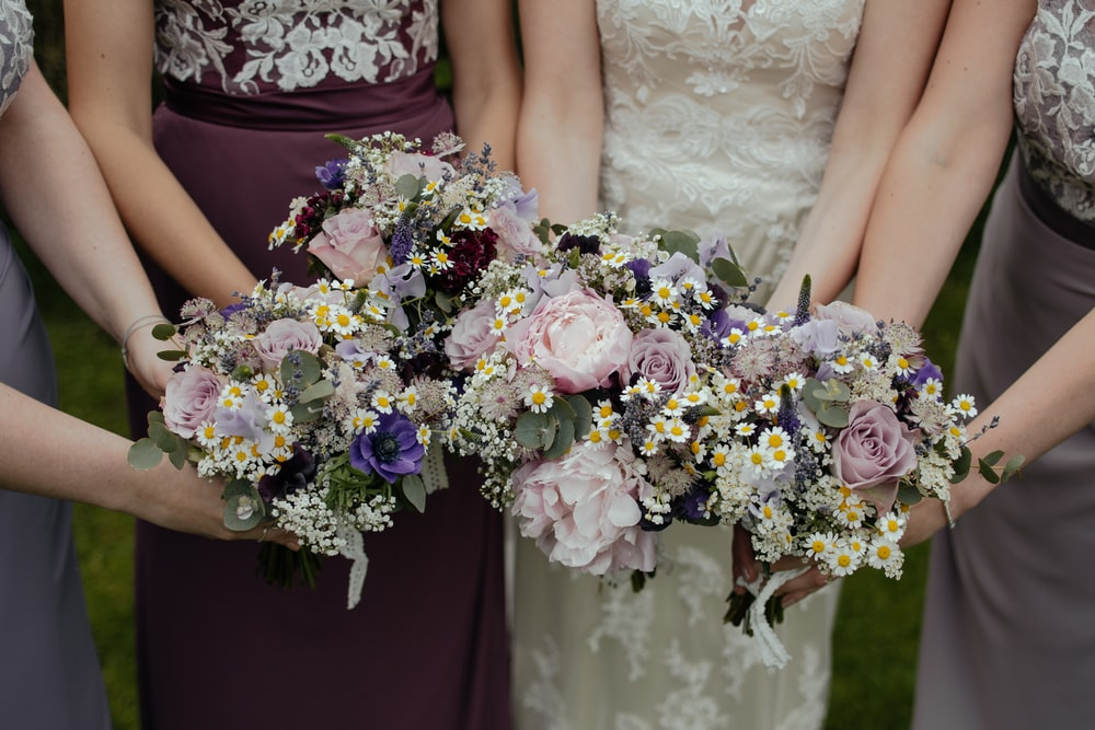 four women carrying bouquet of flowers