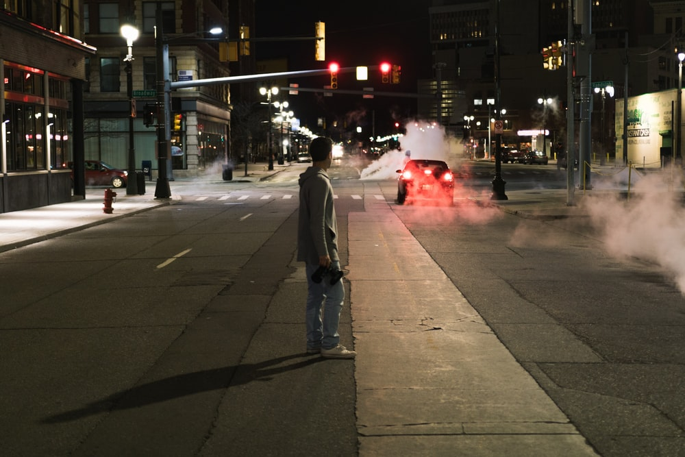 man standing on middle of street while looking at car
