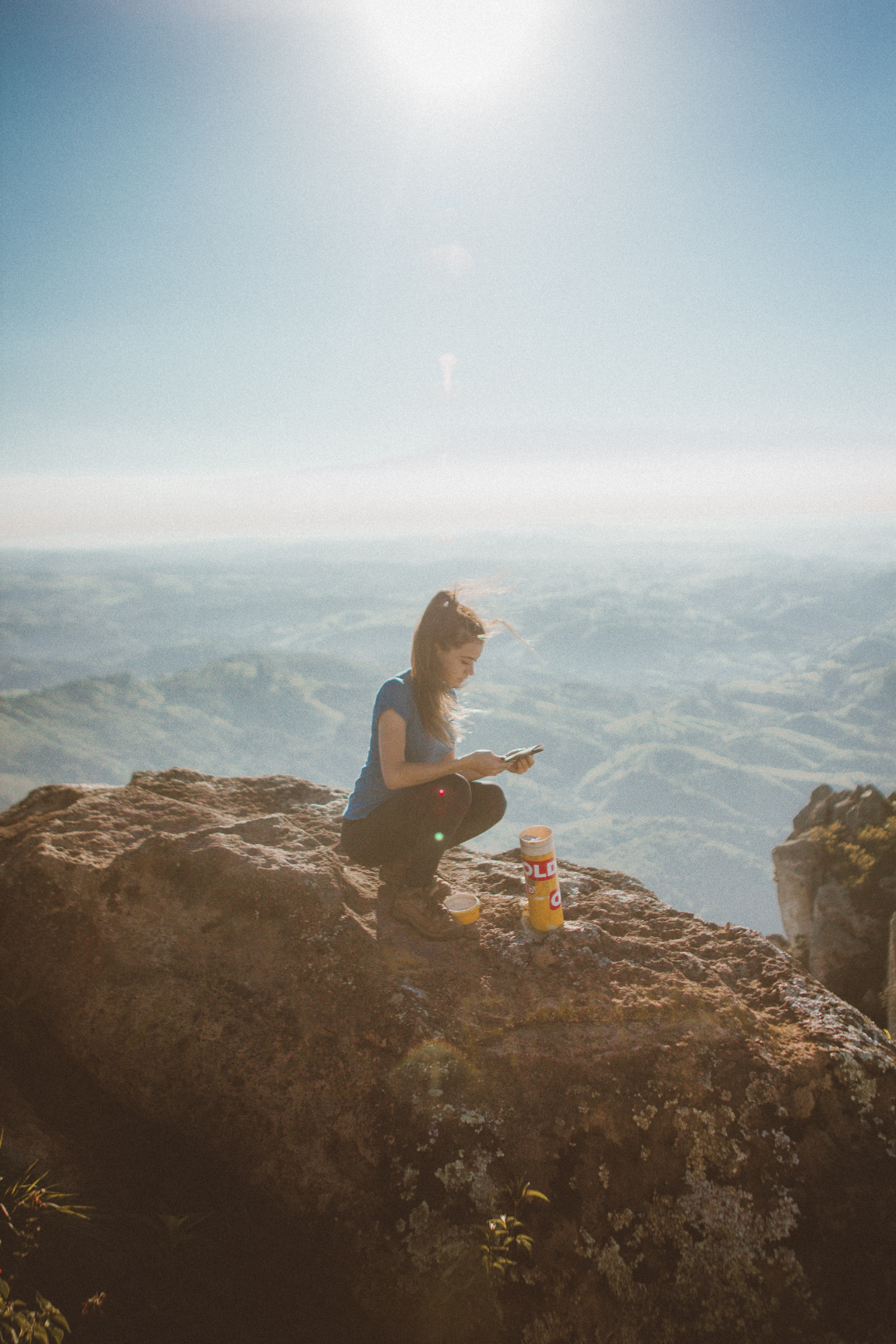 woman holding smartphone while sitting beside orange bottle on top of rock formation