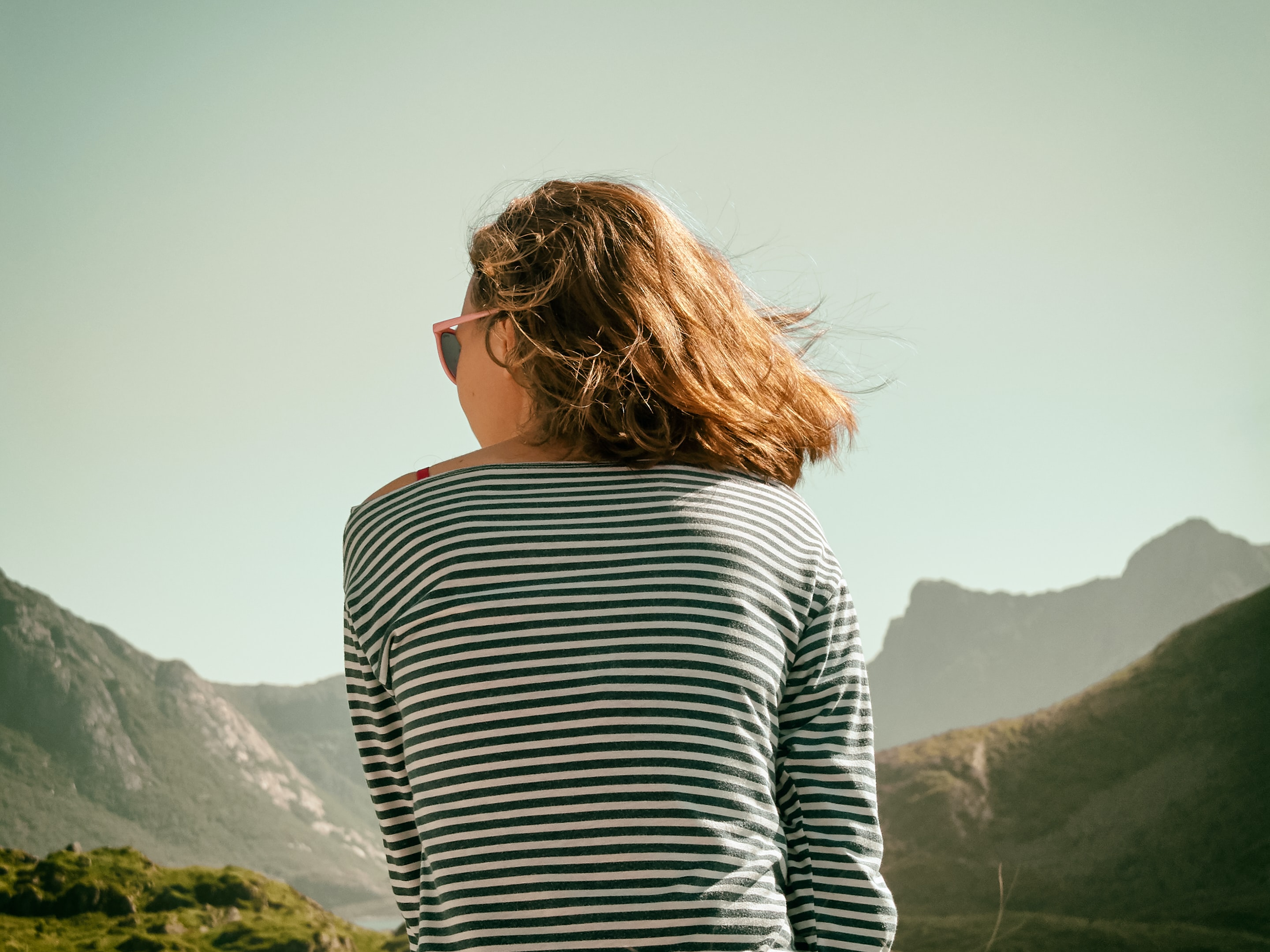 woman with sunglasses sitting on mountain during daytime