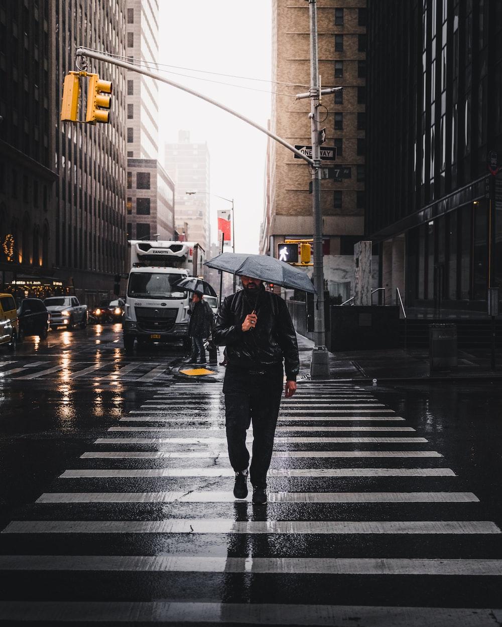 man holding umbrella walking on pedestrian lane