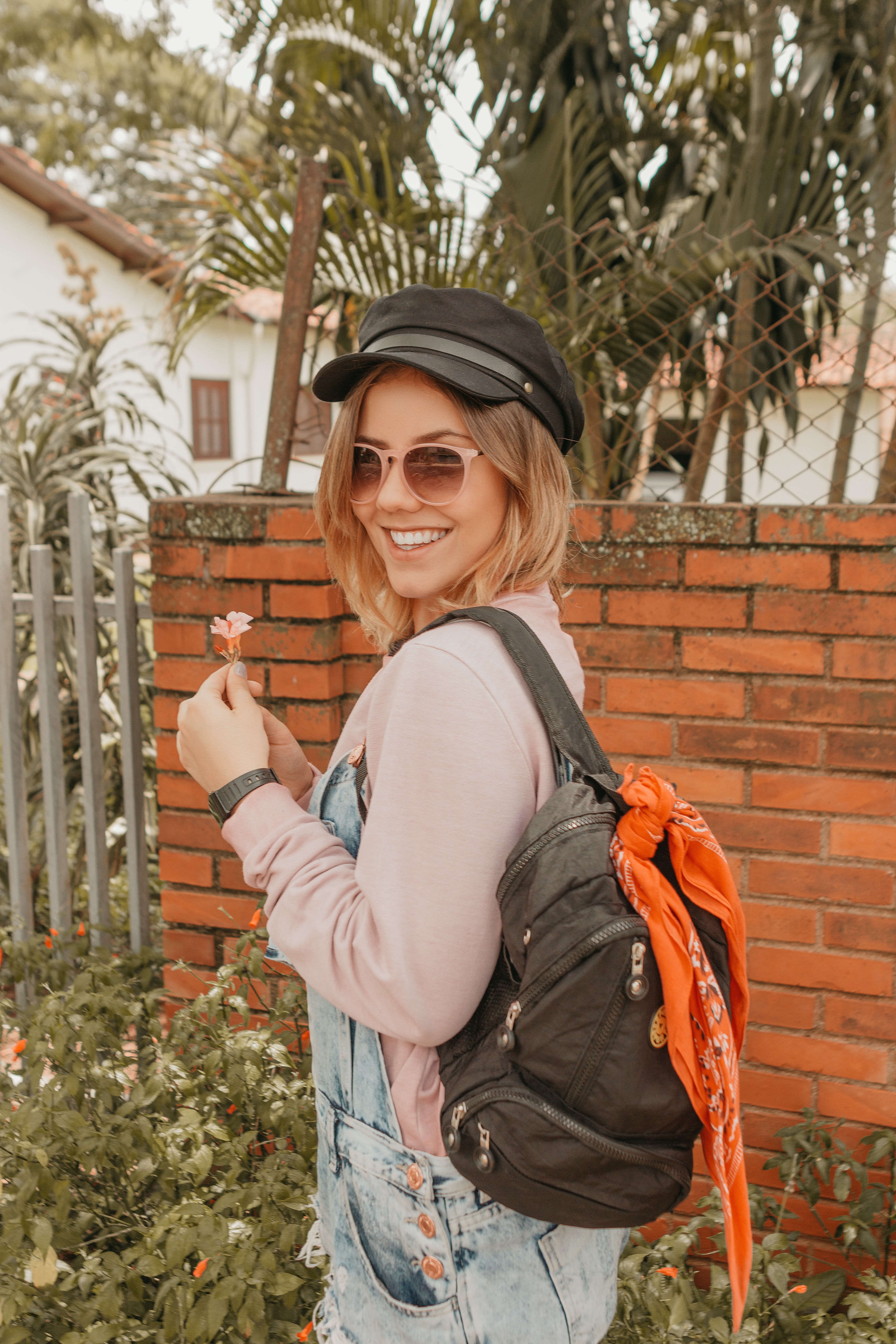 woman holding pink flower while carrying backpack