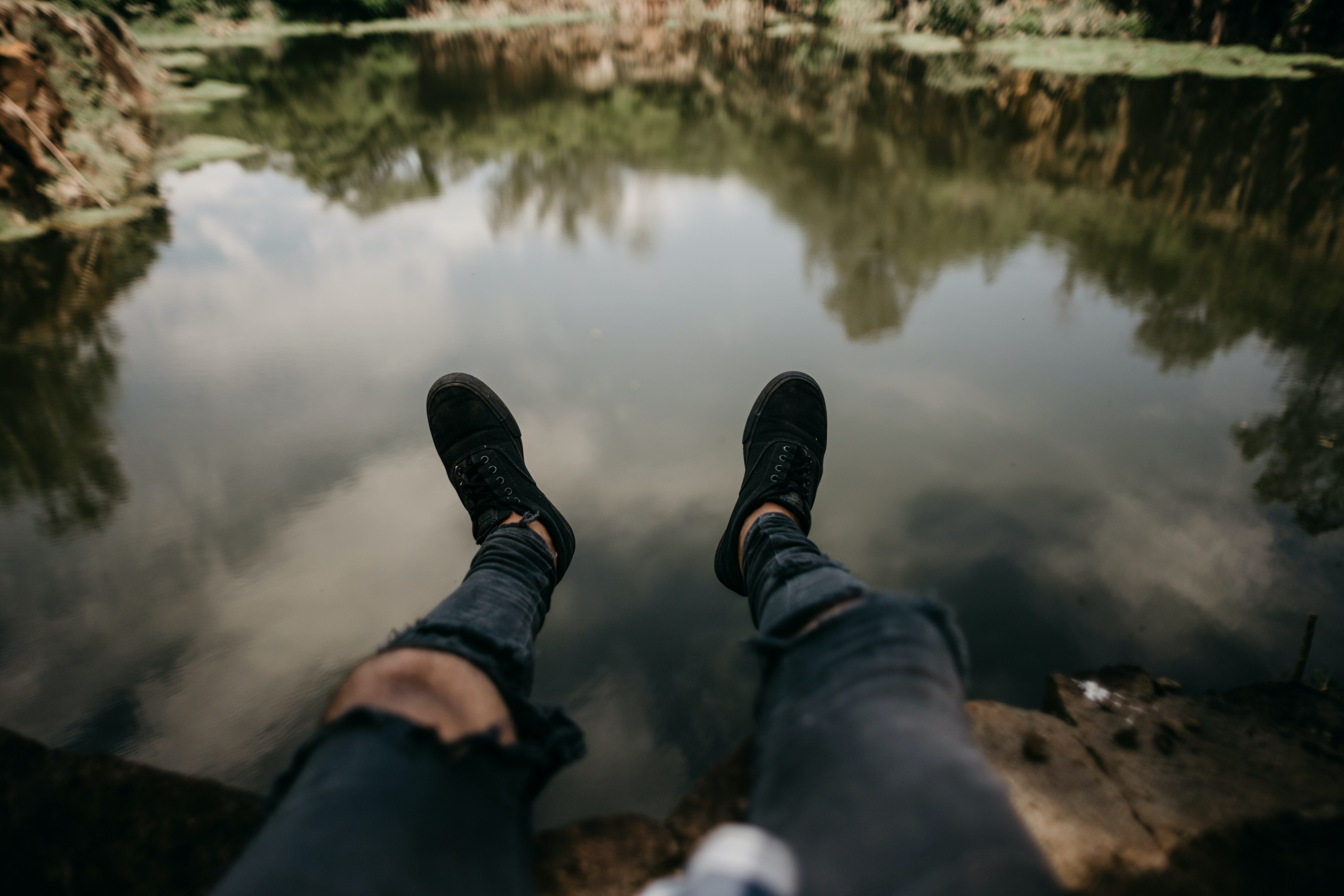 person sit on cliff near body of water