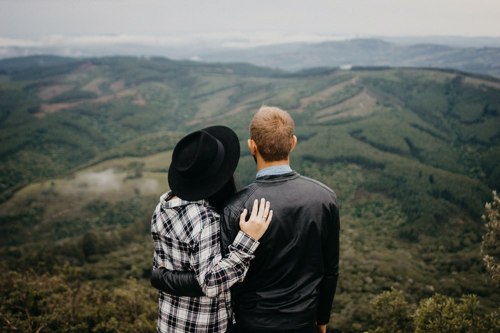 shallow focus photography of man and woman looking down from mountain
