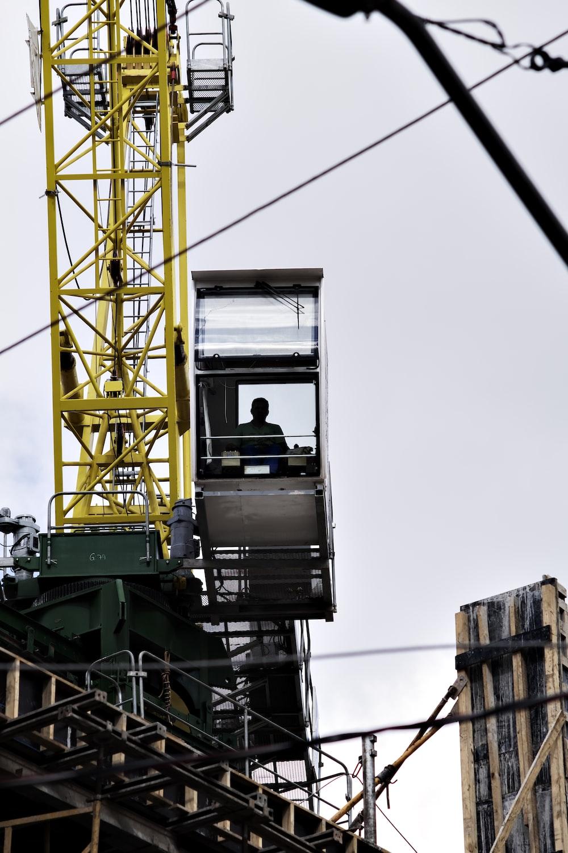 man sitting on crane tower