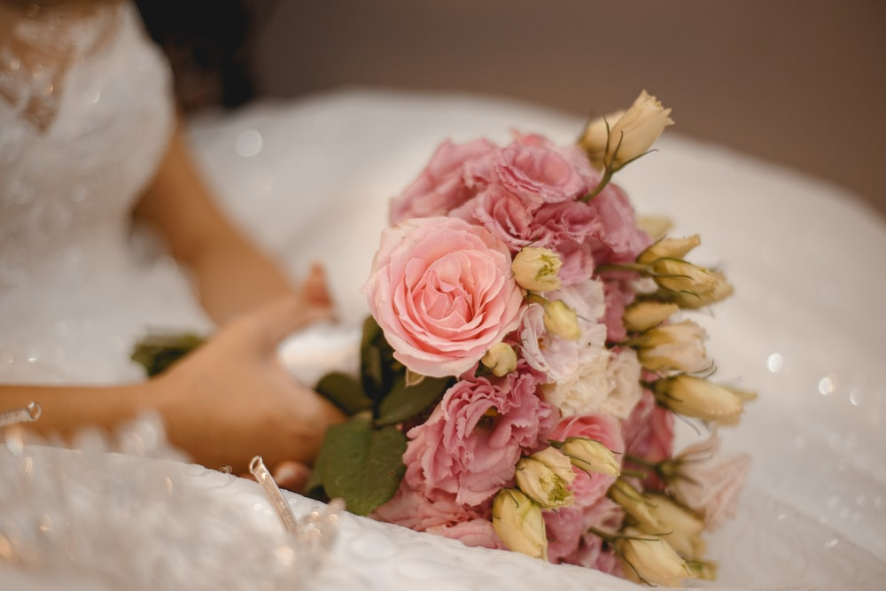 woman in white wedding dress holding pink and white flower bouquet