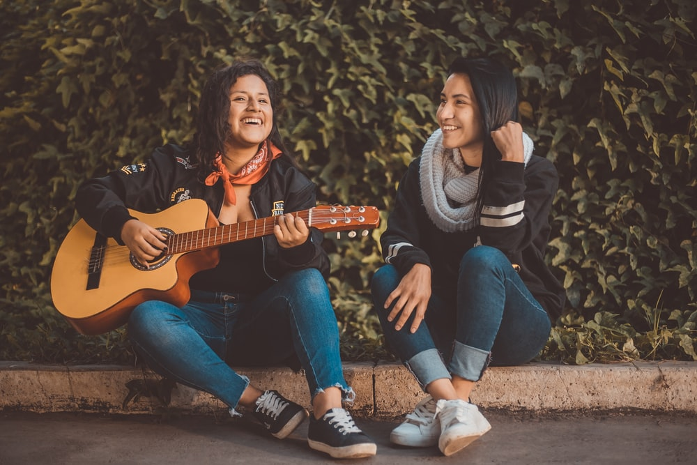 woman playing guitar sitting beside with woman wearing scarf