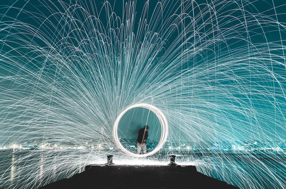 man standing on dock steel wool photography